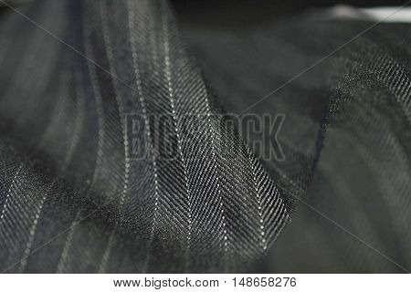 close up roll gray fabric of suit photo shoot by depth of field for object