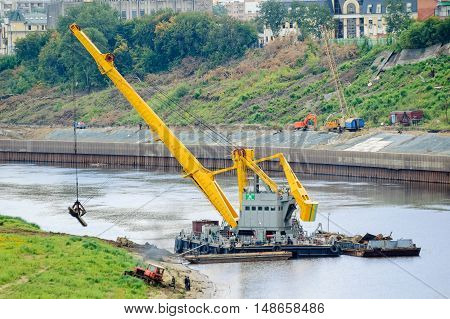 Tyumen, Russia - August 19, 2006: Floating crane excavates sand for quay construction on other bank of Tura river