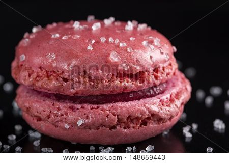 Close up of one pink macaroon cake with sugar over black background