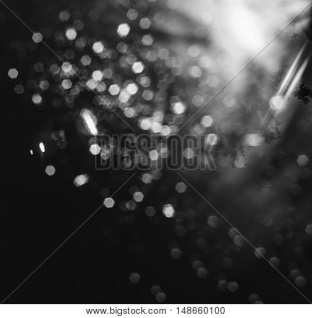 Black and white photo of the night blurred lights - bokeh background photo on the street