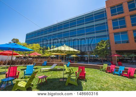 Mountain View, CA, USA - August 15, 2016: dining and relaxing area with parasols and deck chairs for sunbathing for Google employees at Google's headquarters or Googleplex.