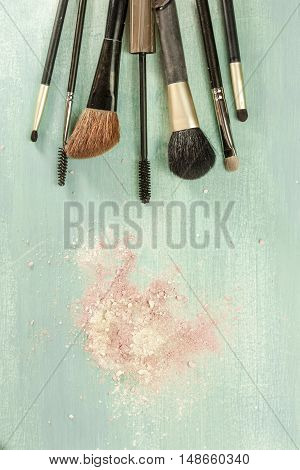 Makeup brushes on a teal blue background, with traces of powder on it. A vertical template for a makeup artist's business card or flyer design, with plenty of copyspace