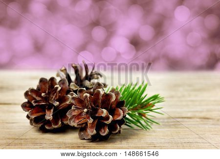 Pine cones on a wooden board against christmas bokeh background.