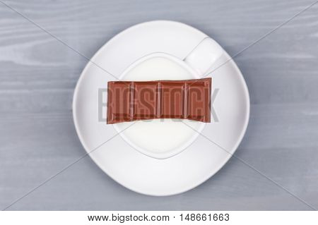 Bar of milk chocolate on a white cup of milk on grey natural wood background. Top view. Concept of making hot drink for autumn fall season.