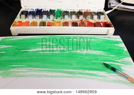 Workplace of artist painter designer student with painted  watercolor splash green grunge paper texture, paintbrush and paints palette on black wooden table background. Art design creative lifestyle leisure time concept