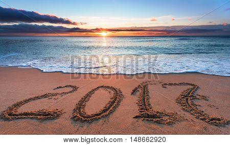 2017 written in sand on tropical beach