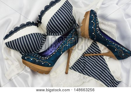 Sexy blue lingerie and denim shoes with rhinestones lying on white satin