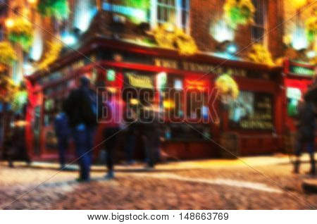Blurred travel backgrounds - Nightlife at popular historical part of Dublin, Ireland - Temple Bar quarter. The area is the location of many bars, pubs and restaurants. People walking inside a pub