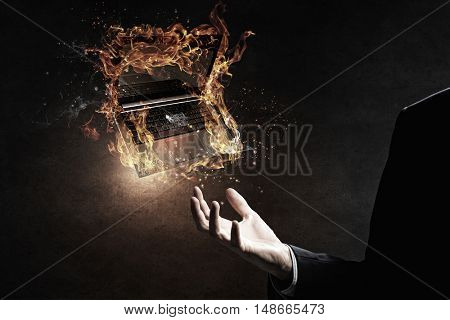 Laptop burning with fire . Mixed media