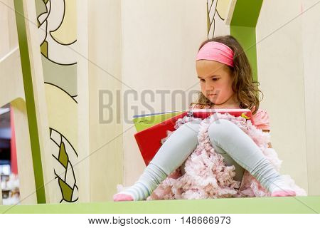 portrait of young happy child girl reading a book