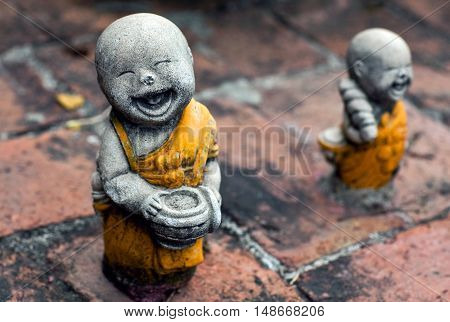 AYUTTHAYA, THAILAND - DECEMBER 30, 2012: Sculpture of little monks with bowls at the buddhists temple in Ayutthaya, Thailand