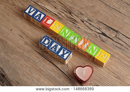 Valentine Day. Spelled with colorful alphabet blocks and a candle in a heart shape