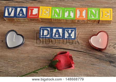 Valentine Day. Spelled with colorful alphabet blocks a red rose and two heart shape candles.