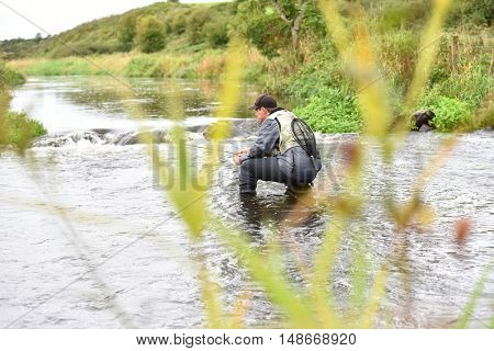 Fly-fisherman knelt in river