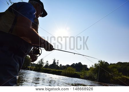 Fisherman in river, afternoon light