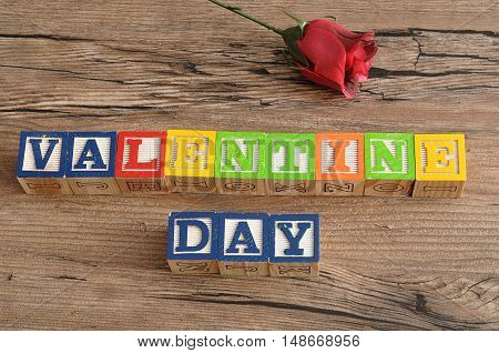 Valentine Day. Spelled with colorful alphabet blocks and a single red rose