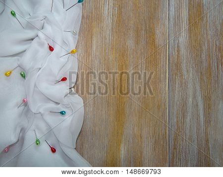 the white cloth laid in folds which stuck needles lying on the wooden boards