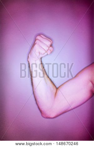 Closeup of man flexing biceps against gray background