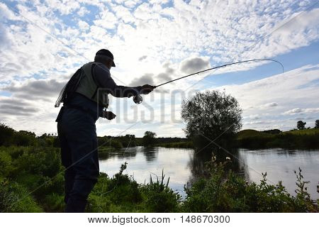 Fisherman in river, evening sunlight