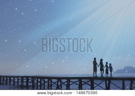 Full length of silhouetted parents and two children holding hands on jetty