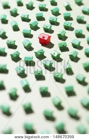 Large group of green model houses with one red in middle