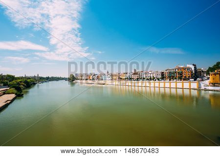 Embankment Of The Guadalquivir River In The City Of Seville, Andalusia, Spain. Sunny Summer Cityscape