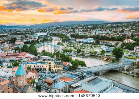 Evening View Of Tbilisi At Colorful Sunset, Georgia. Summer Cityscape. On Photograph Visible The Bridge Of Peace And A New Concert Hall.