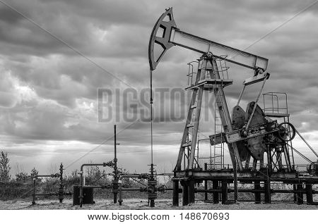Oil rig and wellhead in the oilfield. Gray sky background. Oil and gas concept. Toned.