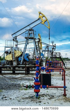 Pump jack and wellhead in the oilfield. Sunset blue sky background. Oil and gas concept. Toned.