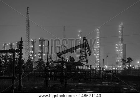 Group of oil rigs and wellhead at the background of refinery by night. Oil and gas industry. Black and white.