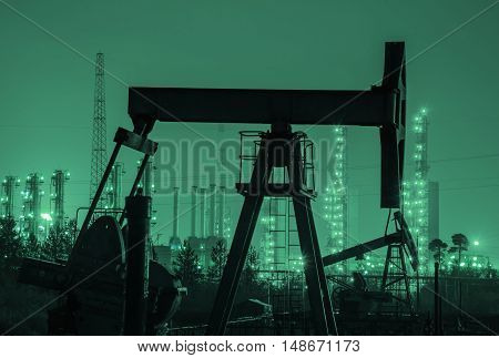 Oil rig silhouette at the background of refinery by night. Oil and gas industry. Toned.