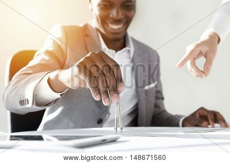 Flare Sun. African Engineer In Stylish Gray Suit Sitting At His Desk With Copy Space Tablet And Draw