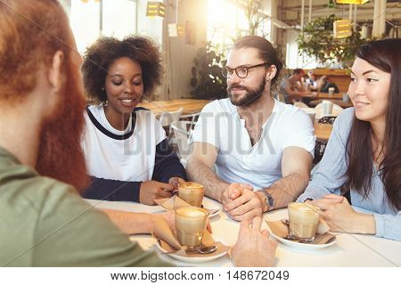 Group Of Young Ambitious People Of Diverse Ethnicities Chatting At Coffee Shop, Discussing New Busin