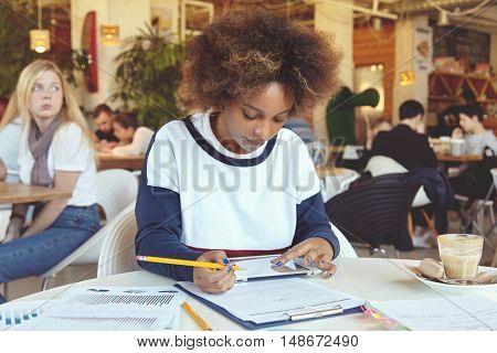 Dark-skinned Student Girl Holding Her Fingers On Touch Screen Tablet, Doing Home Assignment, Prepari