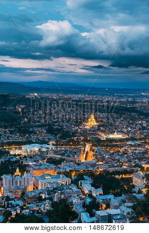 Tbilisi, Georgia. Aerial Cityscape View Of Capital In Evening Illimination, Modern Uptown, Baratashvili Bridge, Sameba Holy Trinity Cathedral. Dramatic Blue Cloudy Sky Of Sunset Over Hilly Area.