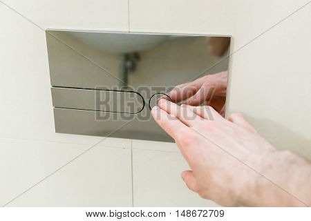 man finger pushing button and flushing toilet
