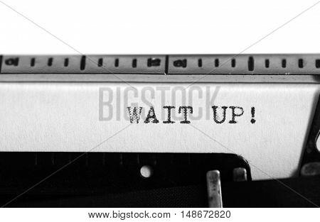 Typewriting on an old typewriter. Typing text: Wait up!