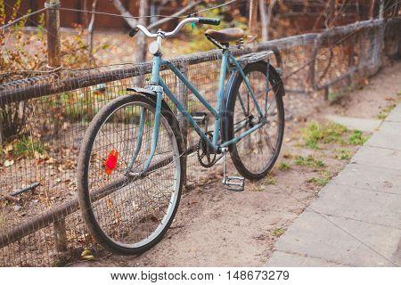 Parked Vintage Old Bicycle Bike In Courtyard. Autumn Season