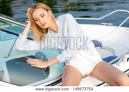 model tests of fashion blond girl in shirt posing in the dock by the sea