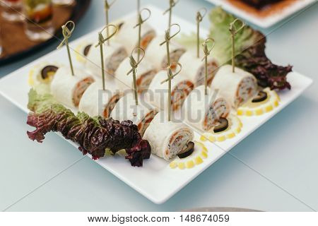 Lavash rolls stuffed with salmon, cheese and sauce., laid on a white glass plate