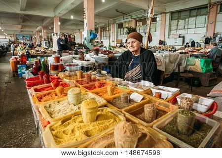 Batumi, Georgia - May 28, 2016: The Elderly Georgian Woman, The  Seller Of Aromatic Varicolored Spices Is Waiting For The Buyers At The Counter Of Covered Market Bazar.