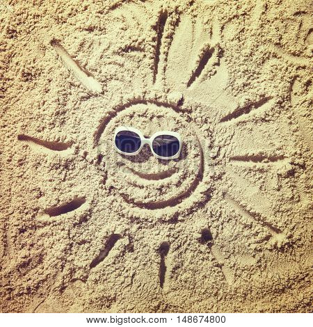 Top view of sandy beach with smiling sun face and sunglasses