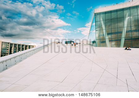 Oslo, Norway. The Groups Of People Going Up On The Slope Of Angled Roof Of Oslo Opera And Ballet House In Summer Day With Cloudy Sky.