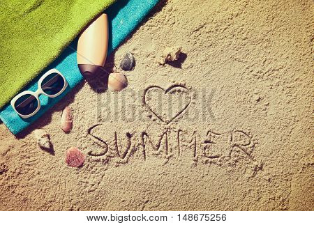 Top view of sandy beach with summer accessories and love sing and summer text