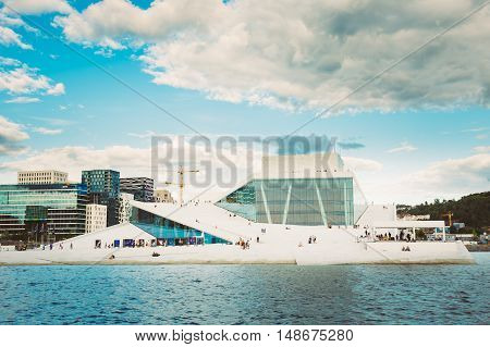 Oslo, Norway - July 31, 2014: The Scenic Cityscape Of  Opera And Ballet House, Ultramodern Building With Glass Facade And Angled Roof To Ground Level Creating A Plaza Inviting Pedestrians To Walk Up And Enjoy Views.