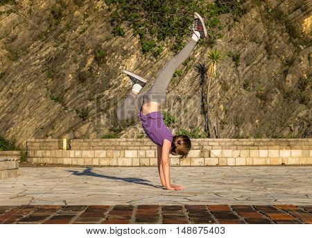 The girl is engaged in acrobatics in the backdrop of the old city wall in Montenegro