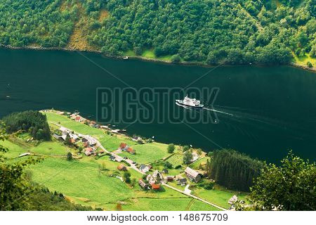 Pleasure Tourist Boat Ship Are Sailing Between Fjords. Picturesque Village Near Sognefjord Fjord In Norway. Amazing Nature Of The Norwegian Mountains. Beautiful Landscape. Travel Concept. Scenic View From Mountain Top.