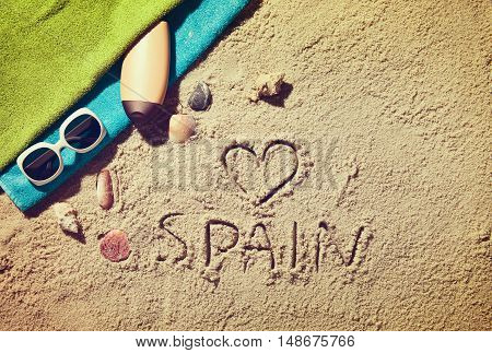 Top view of sandy beach with summer accessories and love sing and Spain text