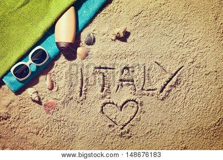 Top view of sandy beach with summer accessories and love sing and Italy text
