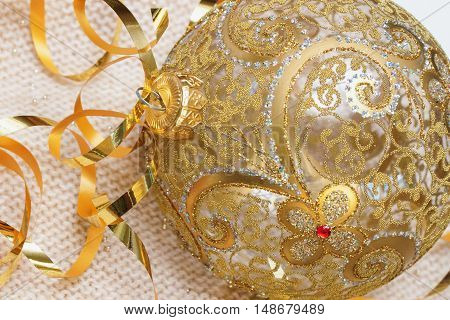 Golden Christmas ball with ribbons decoration glass ball on a light knitted scarf, Christmas and New Year's concept. With place for your text